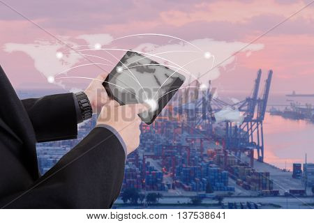hand presses on world map with digital tabletIndustrial Container Cargo freight ship at dusk for Logistic Import Export background (Elements of this image furnished by NASA)