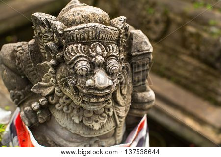 Traditional demon guard statue carved in stone, Bali island, Indonesia.