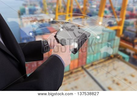 hand presses on world map with digital tablet Industrial Container Cargo freight ship at dusk for Logistic Import Export background (Elements of this image furnished by NASA)