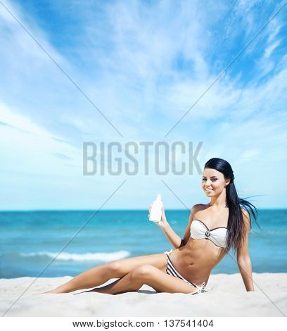 Hot and sexy smiling brunette lying on sand with a bottle of sunscreen lotion over ocean background.