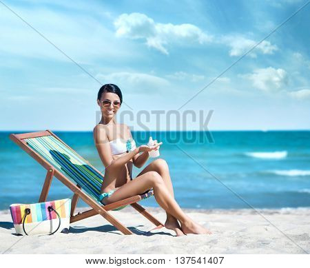 Beautiful happy brunette in sexy swimwear sitting on sunbed and using a sunscreen lotion over ocean background.