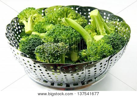 A strainer with fresh Brocclli florets on white background with selective focus.