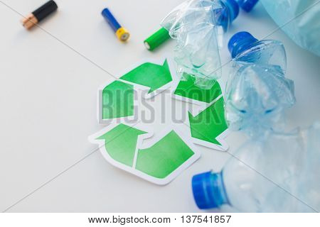 waste recycling, reuse, garbage disposal, environment and ecology concept - close up of used crashed plastic water bottles and batteries with rubbish bag and green recycle symbol