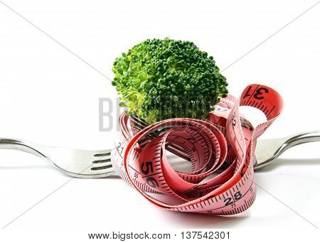 A health concious concept with a broccoli floret on a fork with measuring tape on white background.