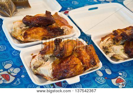Grilled chicken slices in foam box at Thai market