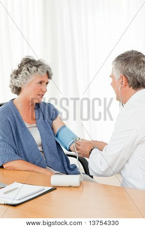 A senior doctor taking the blood pressure of his patient in his office