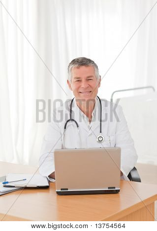 A senior doctor working on his laptop in his office