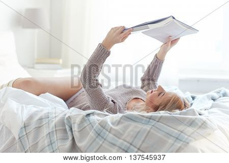 rest, comfort, leisure and people concept - happy young woman reading book in bed at home bedroom