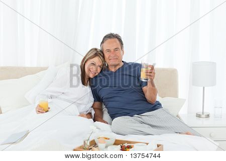 Lovely couple  having breakfast in their bed at home