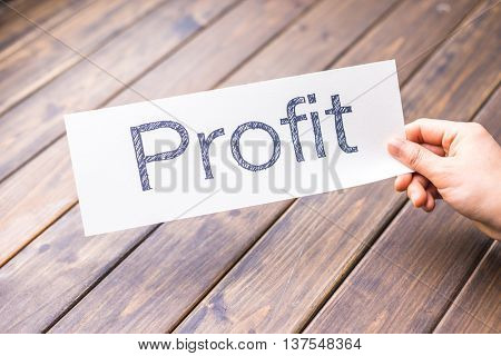 hand hold white paper with word profit