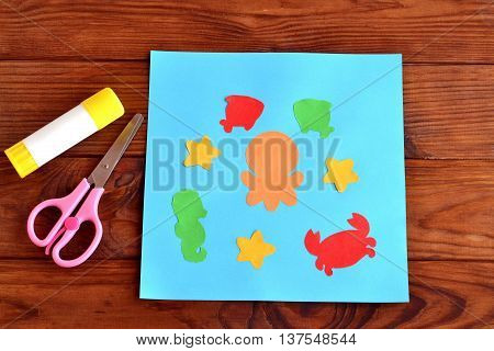 Paper card with sea animals and fishes. Creative ocean creatures crafts for kids. Paper octopus, fish, starfish, seahorse, crab project for children. Scissors, glue on a wooden table