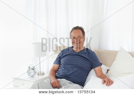 Senior man lying down in his bed at home
