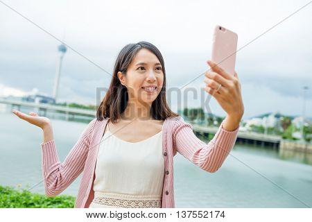 Woman taking photo by herself with mobile phone in Macao city
