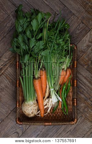 large wooden crate full of raw freshly harvested vegetables. Carrots parsnip peppers.