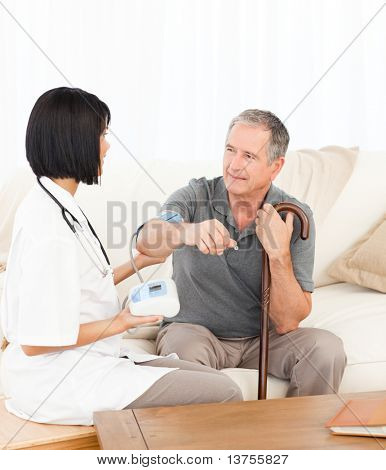 Nurse taking blood pressure of her patient