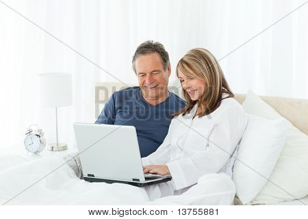 Mature lovers looking at their laptop at home