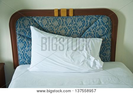 white bed and one white pillow in bedroom