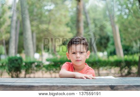 The boy sits at a table in the park and looking straight.