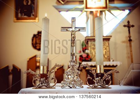 cross and two candles on the table in the Catholic Church