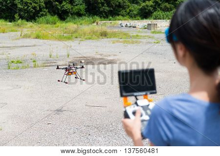 Woman holding radio controller with the drone