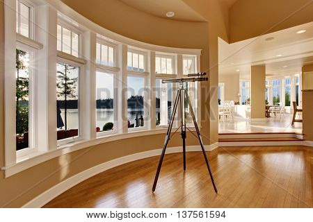 Interior Of Large Living Room With Telescope By Large Six Pane Window.