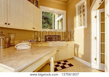 Bright Kitchen Room Area With White Cabinets, Granite Counter Top And Tile Floor
