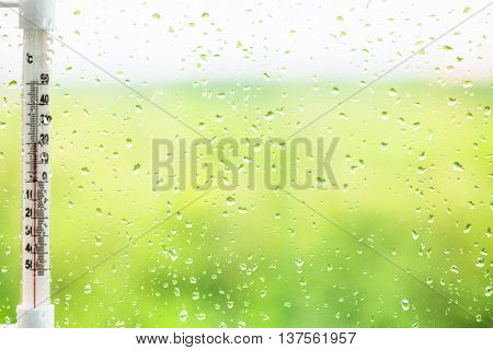 Raindrops On Window Pane And Thermometer