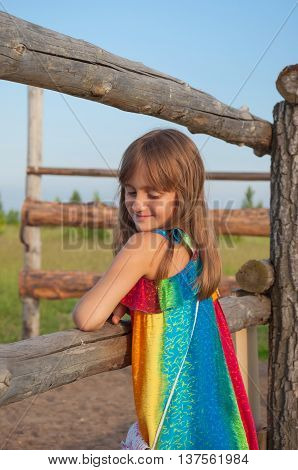 Shy, confused little girl standing near the fence in the countryside