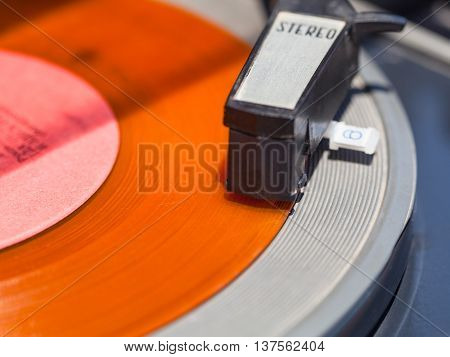 tonearm of record-player on orange vinyl disc close up