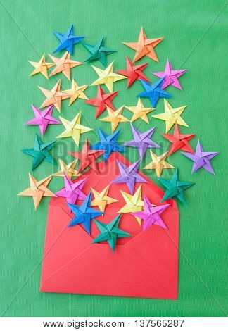 Colorful origami stars for christmas on green