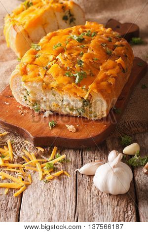 Loaf Of Bread Baked With Cheddar Cheese, Garlic And Herbs Closeup. Vertical