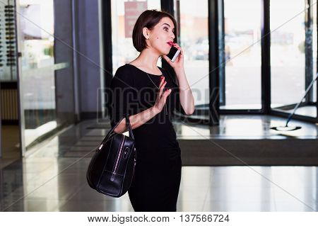 stylish and handsome woman walking and talking on mobile phone in shopping center. surprised emotions on face.