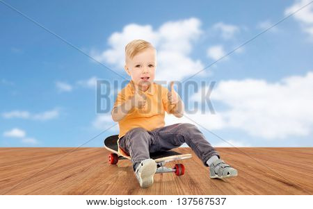 childhood, sport, leisure, gesture and people concept - happy little boy sitting on skateboard and showing thumbs up over blue sky and wooden floor background