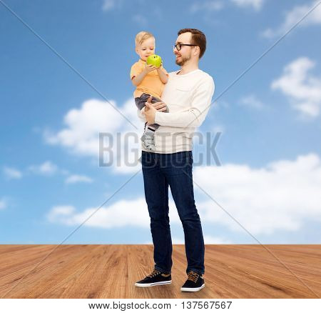 family, childhood, fatherhood, healthy eating and people concept - happy father and and little son with green apple over blue sky and wooden floor background