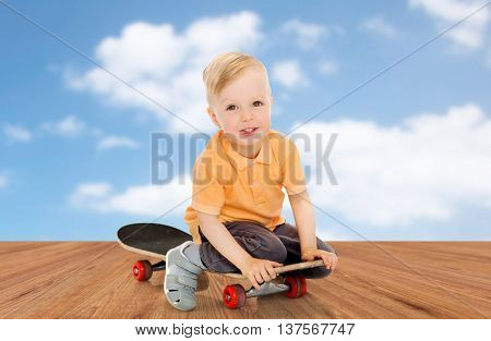 childhood, sport, leisure and people concept - happy little boy sitting on skateboard over blue sky and wooden floor background