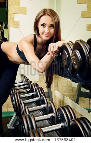 Beautiful young woman with perfect figure is training with dumbbells at the gym. Active lifestyle, bodycare. Fitness equipment.