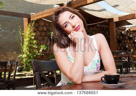 Dreamy Girl Sitting On Terrace Having Coffee