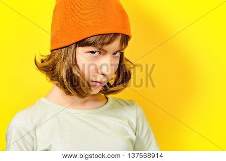 Portrait of a thoughtful and a little bit sad teen girl over yellow background.