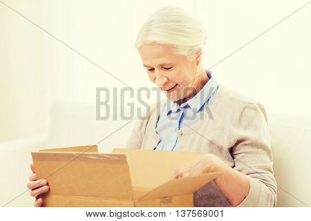age, delivery, mail, shipping and people concept - happy smiling senior woman looking into open parcel box at home