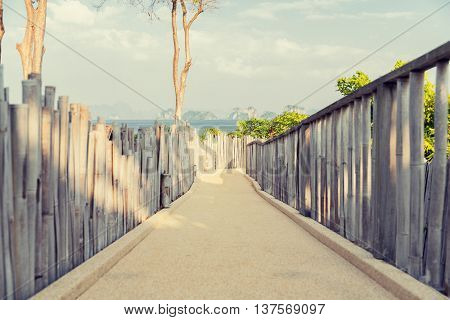 travel, tourism, summer holidays, vacation and leisure concept - road with fence at seaside