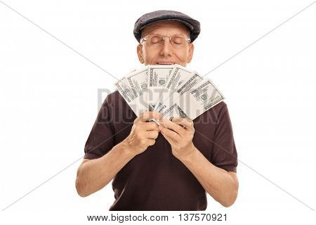 Senior gentleman holding and smelling a few stacks of money isolated on white background