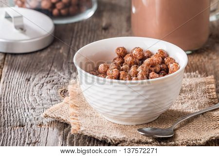 Cereal chocolate balls in bowl with milk on rustic wooden table