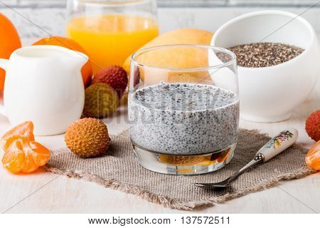 Chia seed pudding  with mangoes and tangerines on glass cup for breakfast on white background.