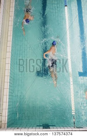 Swimmers doing the freestyle stroke in swimming pool at leisure center