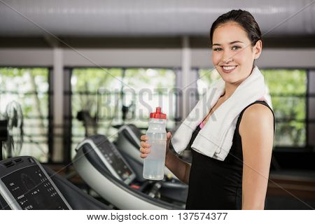 Portrait of happy woman on treadmill holding water bottle at gym