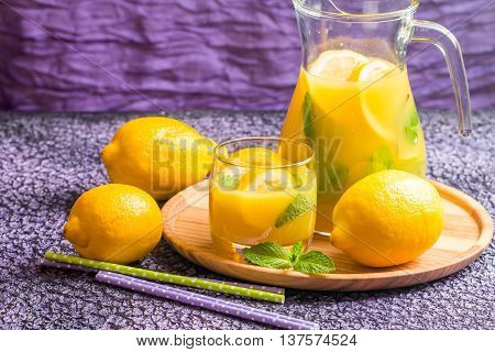 Lemonade drink. Lemonade in the jug and glass with lemons and mint on the table