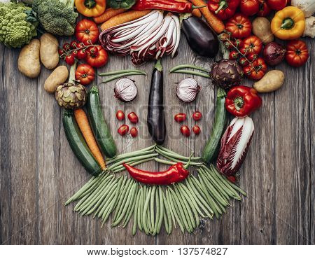 Smiling face of a man with beard made with fresh colorful vegetables on a rustic wooden worktop