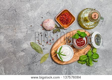 Various dip sauces on gray background, top view