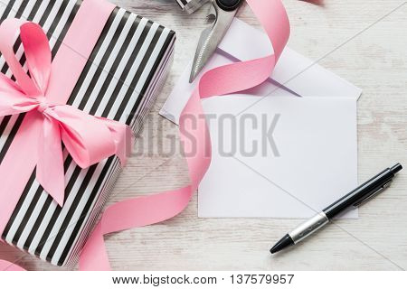 Empty greeting card. Wrapped gift and wrapping materials on a white wood background.