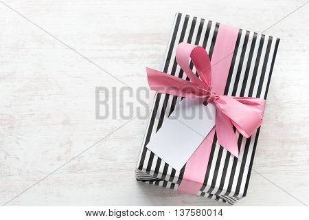 Gift box wrapped in black and white striped paper with pink ribbon on a white wood old background. Empty note tied over.